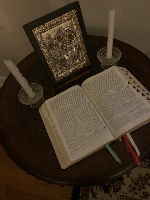 Picture of home bible and icon on table with two candles